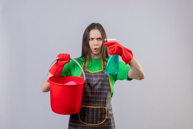 孤立した白い壁に彼女の手にスプレーを掃除するためにバケツを保持している赤い手袋で制服を着ている若い女性を掃除することを懸念