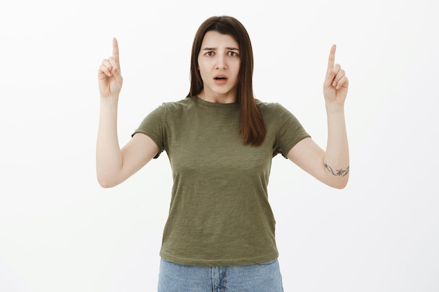 Concerned and confused sad girl cannot understand what happened frowning open mouth in frustration and shock looking nervously as pointing up with raised hands over gray wall