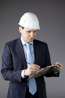 Concerned constructor in white helmet and formal clothing writes on clipboard