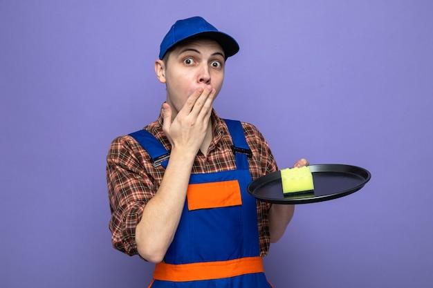제복을 입고 쟁반에 스폰지를 들고 있는 모자를 쓴 손으로 젊은 청소부로 입을 덮은 우려