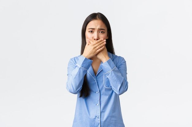 Concerned cute asian girl in blue pajamas frowning and look worried as shut mouth with hands, cover lips, reacting to concerning awful news, standing upset white background.