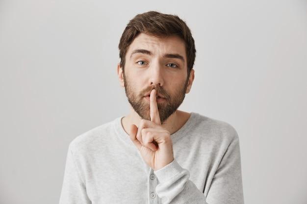 Il simpatico ragazzo barbuto preoccupato mostra il segno di silenzio, dì shh per mantenere la voce bassa