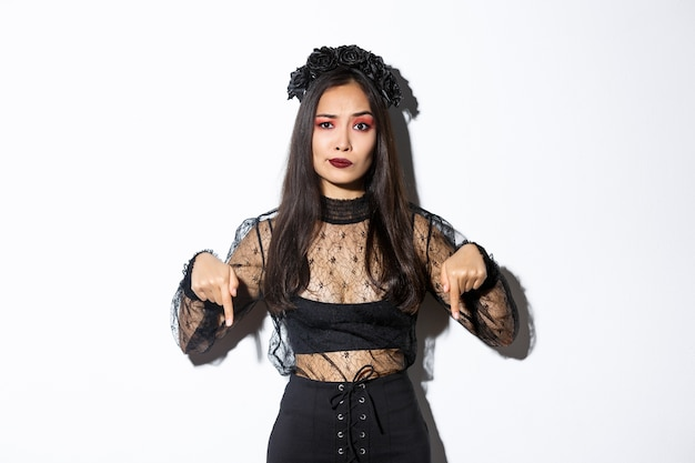 Preoccupata, una donna asiatica delusa in abito di pizzo nero e ghirlanda sorride scettica mentre punta il dito verso qualcosa di brutto, lamentandosi su sfondo bianco.