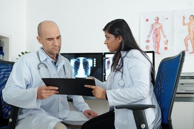 Обеспокоенные врачи обсуждают историю болезни пациента с симптомами коронавируса