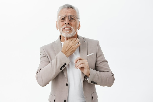 Concerned elderly man touching his neck, complaining sore throat