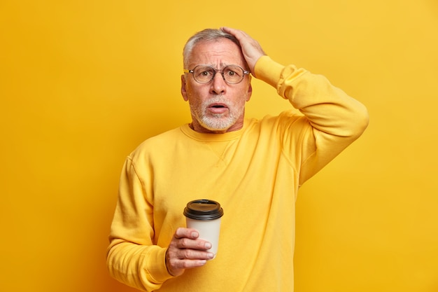 Concerned embarrassed bearded aged man keeps hand on head and stares stupefied at front drinks takeaway coffee dressed in casual jumper isolated over yellow wall cannot believe in failure