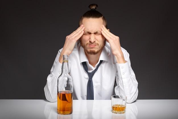 Обеспокоена сотрудник с бутылкой виски