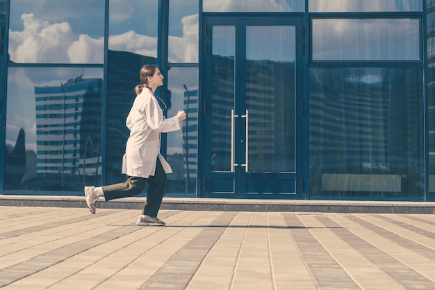 Concerned female doctor quickly runs down the street . photo with a copy-space.