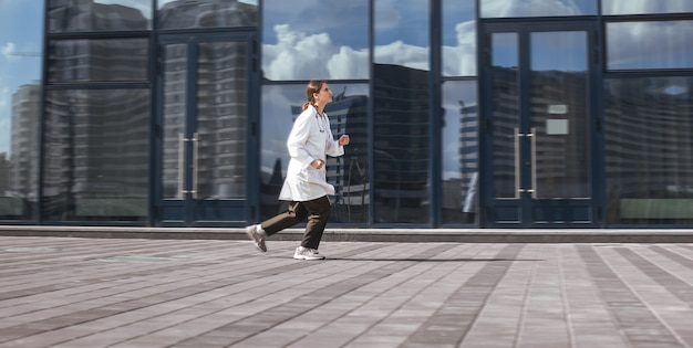 Concerned female doctor quickly runs down the street