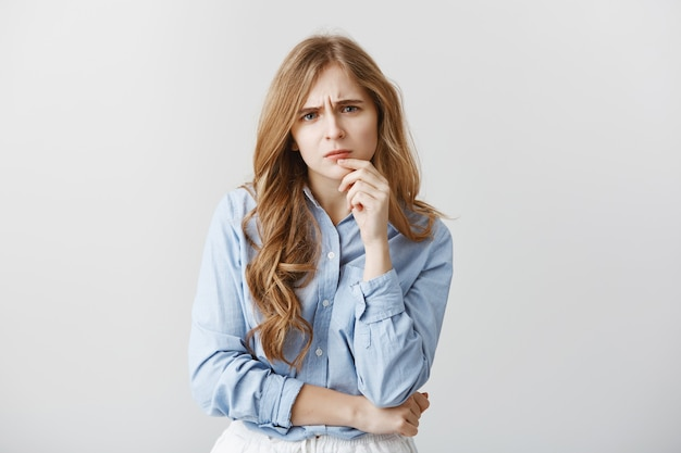 Concerned friend hearing out issue. portrait of attractive caucasian female with blond hair and curls holding hand on lip, frowning, being worried and serious while thinking up solution