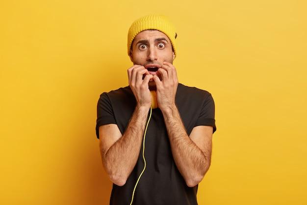心配しているおびえた男はカメラを神経質に見て、パニックで指の爪を噛みます
