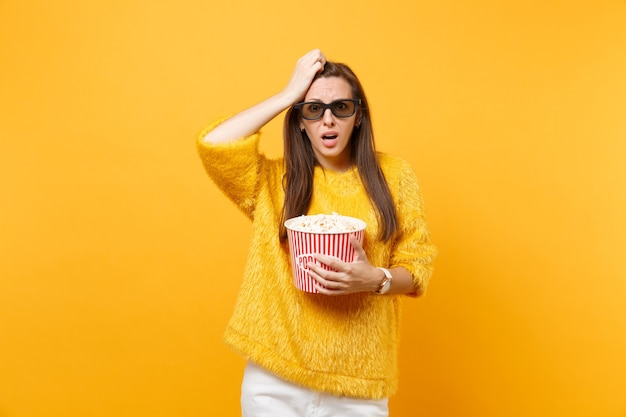 Concerned frustrated young girl in 3d imax glasses putting hand on head watching movie film holding bucket of popcorn isolated on bright yellow background. people sincere emotions in cinema lifestyle.