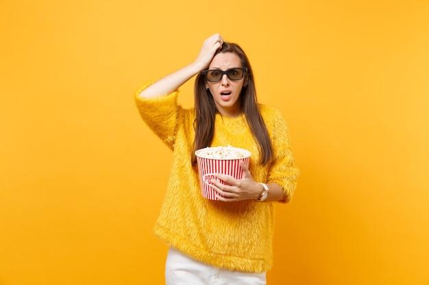 3d 아이맥스 안경을 쓴 어린 소녀가 밝은 노란색 배경에 격리된 팝콘 양동이를 들고 영화 영화를 보고 머리에 손을 얹고 걱정합니다. 영화 라이프 스타일에서 사람들은 진실한 감정.