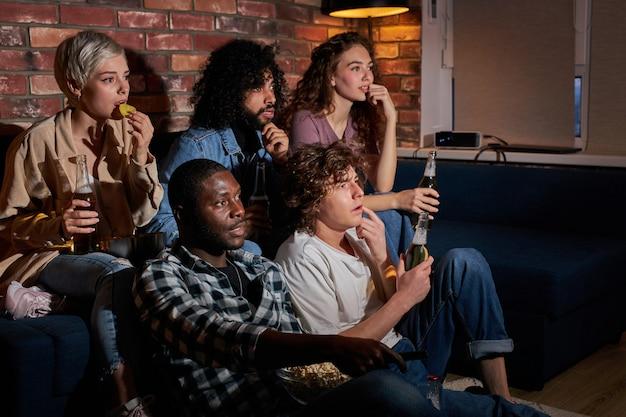 Обеспокоенная группа друзей волнуется, смотря спортивную игру по телевизору, болеет за любимую команду, смотрит на экран телевизора, расстроена игровым процессом, ест чипсы и пьет пиво