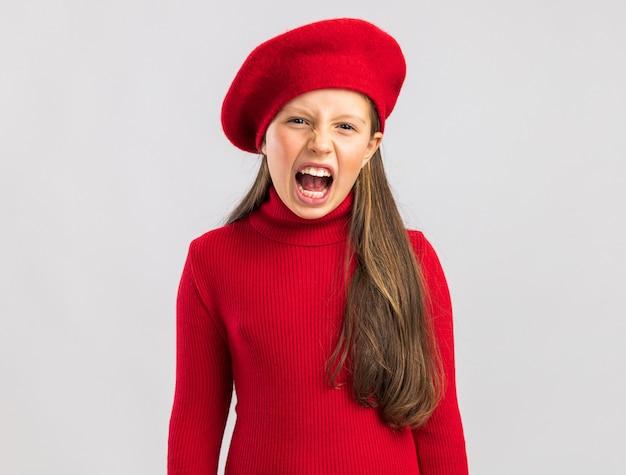 正面を見て赤いベレー帽を身に着けている心配している小さなブロンドの女の子とコピースペースで白い壁に隔離された悲鳴