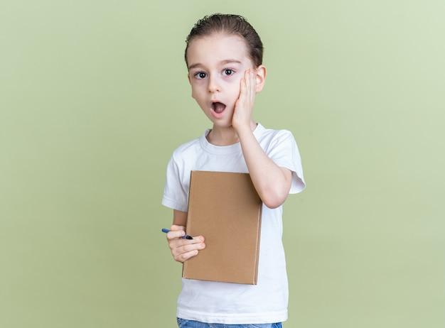 Ragazzino preoccupato che tiene la mano sul viso tenendo il libro guardando la telecamera isolata sul muro verde oliva con spazio per le copie