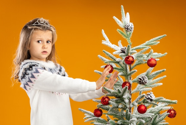 Concerned little girl standing nearby christmas tree wearing tiara with garland on neck holding out hands at tree isolated on orange background