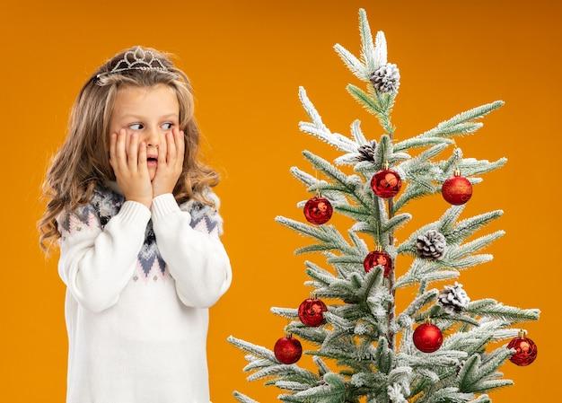 オレンジ色の背景で隔離の手で首に花輪で覆われた頬にティアラを身に着けているクリスマスツリーの近くに立っている心配の少女