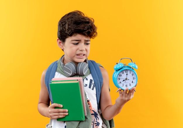 心配している小さな男子生徒がバックバッグとヘッドフォンを身に着けて本を持って、黄色の背景で隔離の彼の手で目覚まし時計を見て