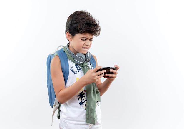 Piccolo scolaro preoccupato che indossa lo zaino e le cuffie che giocano sul telefono