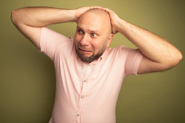 머리 뒤에 손을 잡고 분홍색 티셔츠를 입고 측면 중년 대머리 남자를보고 걱정