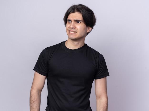 흰 벽에 고립 된 검은 티셔츠를 입고 측면 젊은 잘 생긴 남자를보고 우려