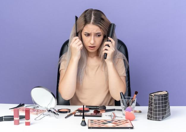 Обеспокоенная глядя вниз молодая красивая девушка сидит за столом с инструментами для макияжа, расчесывая волосы, изолированные на синей стене