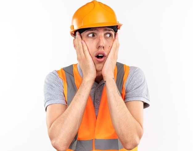 Concerned looking at side young builder man in uniform putting hands on cheeks