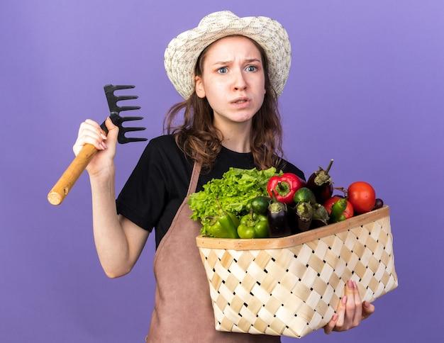 熊手と野菜のバスケットを保持しているガーデニングの帽子をかぶっている心配そうな側の若い女性の庭師