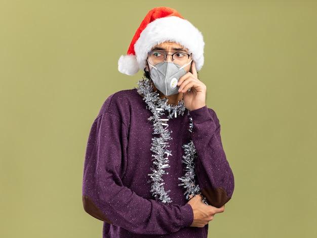 올리브 녹색 배경에 고립 뺨에 손을 넣어 목에 갈 랜드와 함께 크리스마스 모자와 의료 마스크를 착용하는 측면 젊은 잘 생긴 남자를 찾고 우려