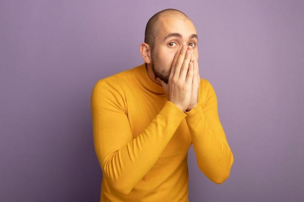 Обеспокоенный смотрящий прямо перед собой молодой красивый парень закрыл лицо руками, изолированными на фиолетовом