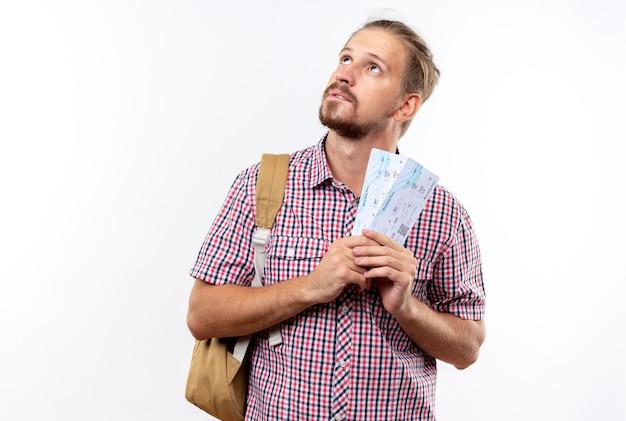 コピースペースで白い壁に隔離されたチケットを保持しているバックパックを身に着けている若い男の学生を見上げることを懸念