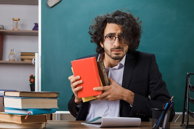 Concerned male teacher wearing glasses holding book sitting at table with school tools in classroom