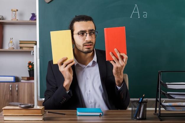 Insegnante maschio interessato con gli occhiali che tiene e guarda il libro seduto al tavolo con gli strumenti della scuola in classe