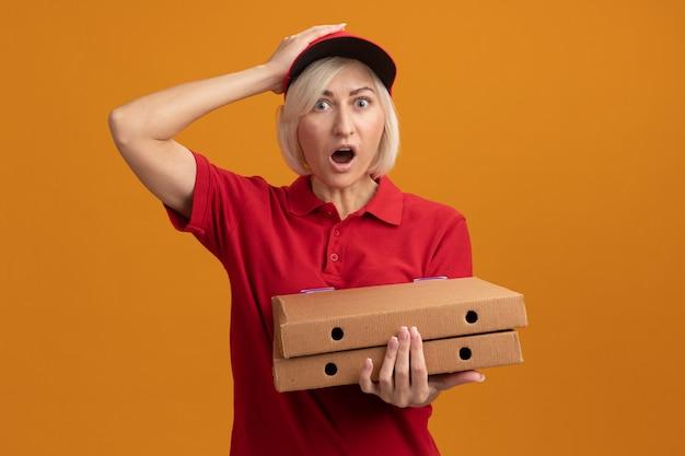 빨간 제복을 입은 중년 금발 배달부 여성, 복사 공간이 있는 주황색 벽에 격리된 머리에 손을 얹고 피자 패키지를 들고 있는 모자