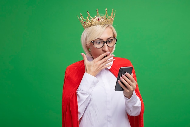 Concerned middle-aged blonde superhero woman in red cape wearing glasses and crown holding and looking at mobile phone keeping hand on mouth isolated on green wall with copy space