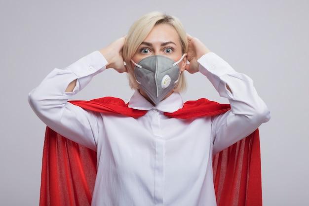 Donna supereroe bionda di mezza età interessata in mantello rosso che indossa una maschera protettiva che mette le mani sulla testa isolata sul muro bianco