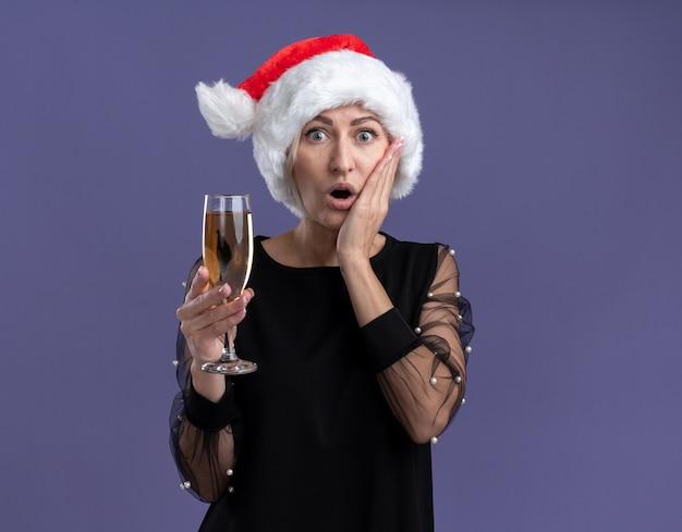 Donna bionda di mezza età interessata che indossa il cappello di natale che guarda l'obbiettivo tenendo il bicchiere di champagne tenendo la mano sul viso isolato su sfondo viola