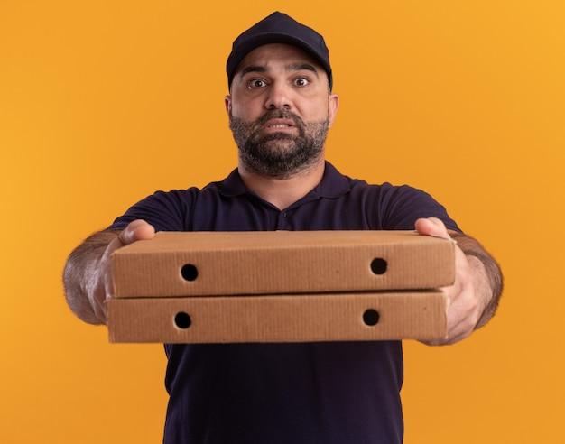 노란색 벽에 고립 된 앞에 피자 상자를 들고 유니폼과 모자에 우려 중년 배달 남자