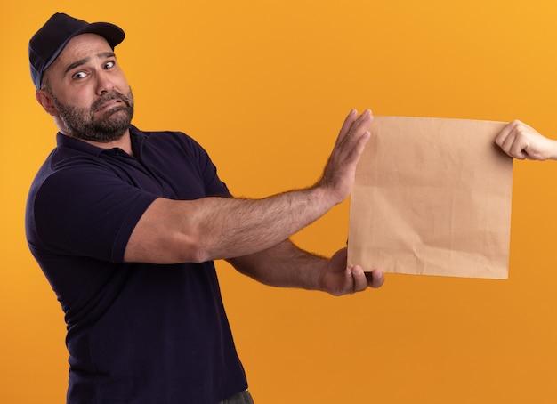 Uomo di consegna di mezza età interessato in uniforme e cappuccio che dà il pacchetto di cibo di carta al cliente isolato sulla parete gialla
