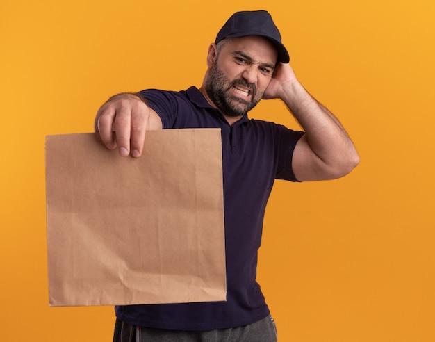 Uomo di consegna di mezza età interessato in uniforme e cappuccio che tiene e che esamina il pacchetto di cibo di carta che mette la mano sulla testa isolata sulla parete gialla