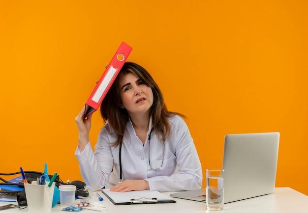 コピースペースのある孤立したオレンジ色の壁に頭にフォルダーを置く医療ツールを備えたラップトップでデスクワークに座って聴診器で医療ローブを身に着けている懸念の中年女性医師