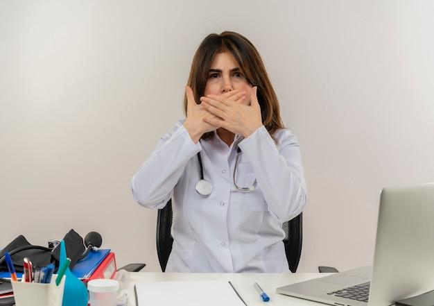 Medico femminile di mezza età interessato che indossa la veste medica con lo stetoscopio che si siede alla scrivania lavora sul computer portatile con strumenti medici ha coperto la bocca con le mani sul muro bianco con lo spazio della copia
