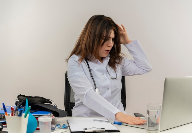 Concerned middle-aged female doctor wearing wearing medical robe with stethoscope sitting at desk work on laptop with medical tools used laptop putting hand on head on white wall with copy space