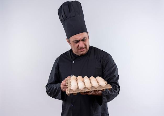 Cuoco maschio di mezza età interessato in uniforme del cuoco unico che esamina le uova in lotti nella sua mano sulla parete bianca isolata