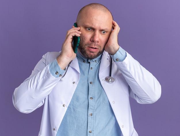 Medico maschio di mezza età interessato che indossa abito medico e stetoscopio parlando al telefono guardando in basso tenendo la mano sulla testa isolata sul muro viola