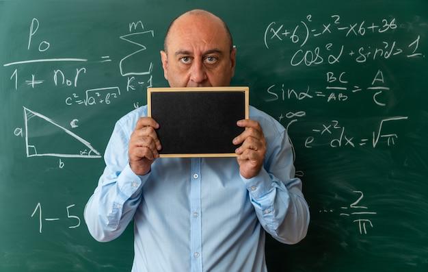 Preoccupato insegnante maschio di mezza età in piedi di fronte alla lavagna con il viso coperto con una mini lavagna