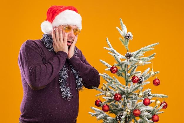 얼굴에 손을 유지 장식 된 크리스마스 트리 근처에 서 안경으로 목 주위에 산타 모자와 반짝이 갈 랜드를 입고 우려 중년 남자