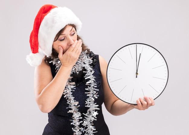 흰색 배경에 고립 된 입에 손을 유지하는 시계를 들고 목 주위에 산타 모자와 반짝이 갈 랜드를 입고 우려 중년 여성