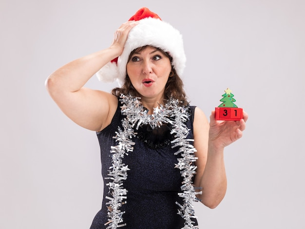 흰색 배경에 고립 된 측면을보고 머리에 손을 유지하는 날짜와 함께 크리스마스 트리 장난감을 들고 목에 산타 모자와 반짝이 갈 랜드를 입고 우려 중년 여성
